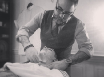 Dino, giving his nephew his first straight razor shave in his barber shop.